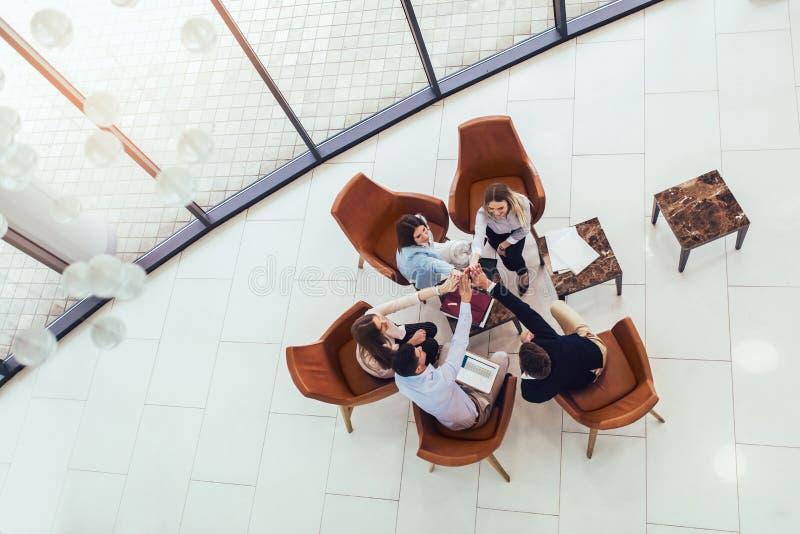 Groupe de jeunes professionnels d'affaires s'asseyant ensemble et ayant la discussion occasionnelle dans le couloir de bureau Vue image stock