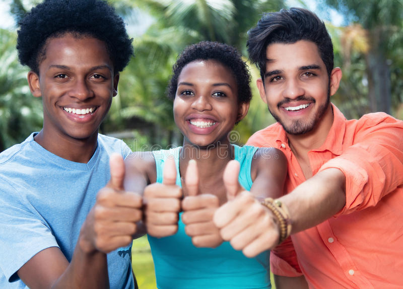 Groupe de l'afro-américain et l'homme et la femme riants de latin montrant le pouce image stock