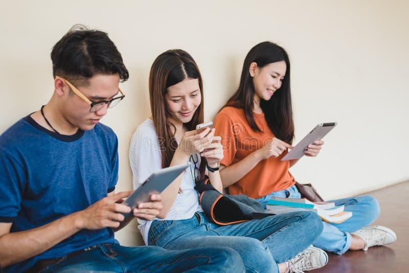 Groupe de l'?tudiant universitaire asiatique ? l'aide du comprim? et du t?l?phone portable en dehors de la salle de classe Bonheu images libres de droits