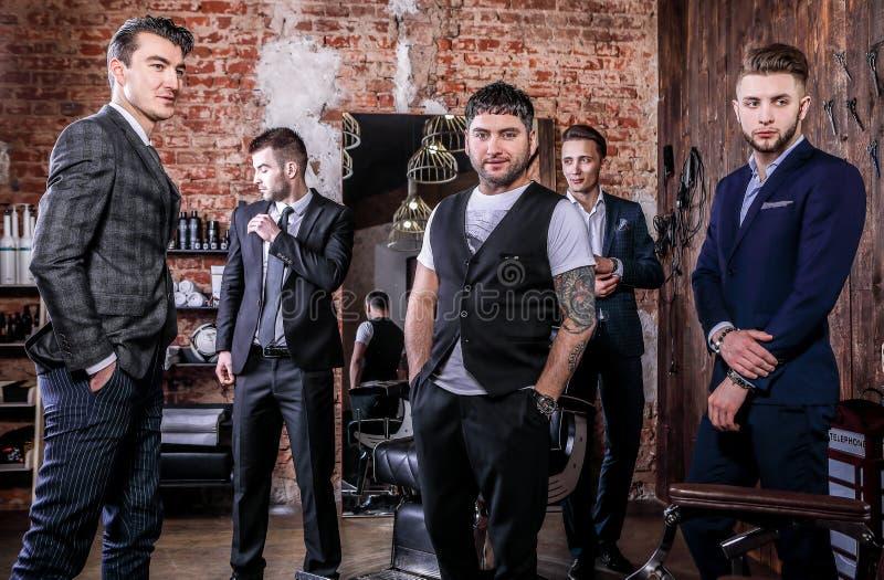 Groupe de la pose des jeunes hommes positifs élégants dans l'intérieur du raseur-coiffeur photo libre de droits