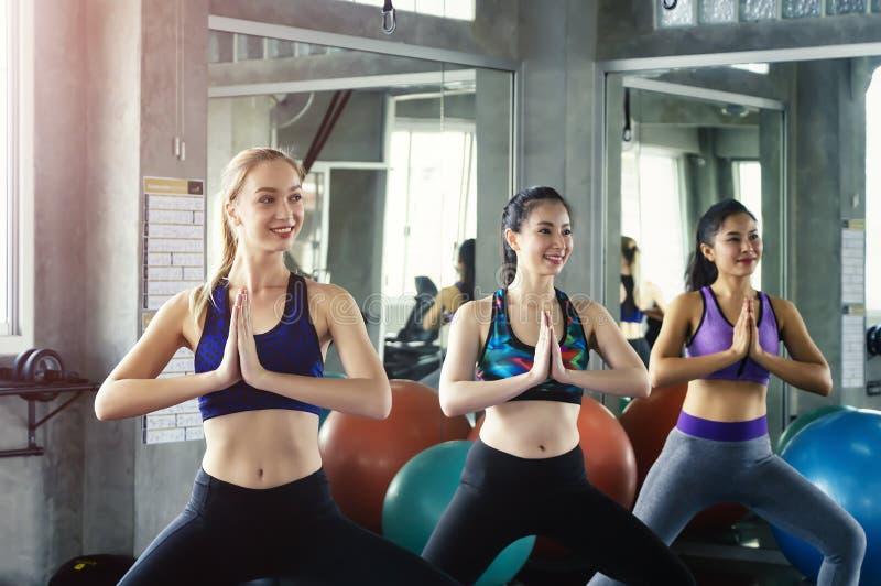 Groupe de leçon de pratique de yoga de jeunes attirants sportifs images stock