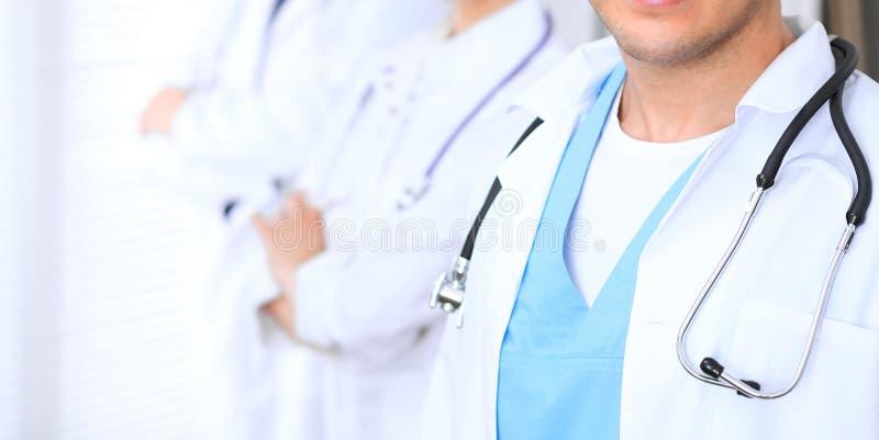 Groupe de los doctores desconocidos que se colocan derecho en oficina del hospital Ciérrese para arriba del estetoscopio en el pe foto de archivo libre de regalías
