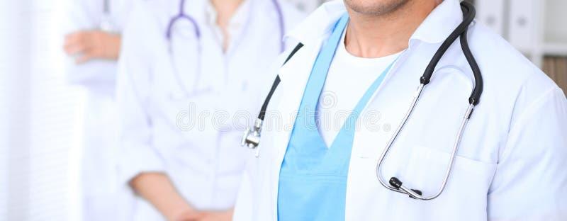 Groupe de los doctores desconocidos que se colocan derecho en oficina del hospital Ciérrese para arriba del estetoscopio en el pe fotos de archivo libres de regalías