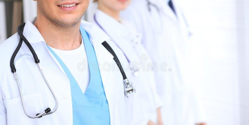 Groupe de los doctores desconocidos que se colocan derecho en oficina del hospital Ciérrese para arriba del estetoscopio en el pe fotografía de archivo libre de regalías