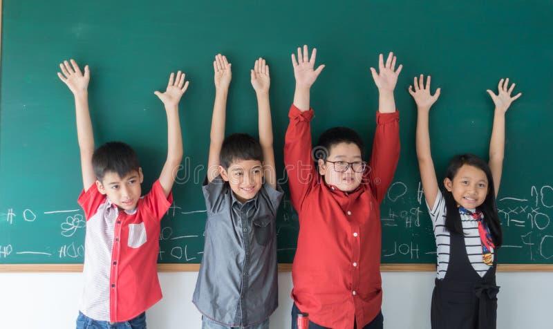 Groupe de mains asiatiques d'étudiant sur le tableau noir photos stock