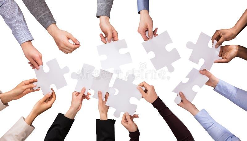 Groupe de mains tenant les casse-tête blancs photo libre de droits