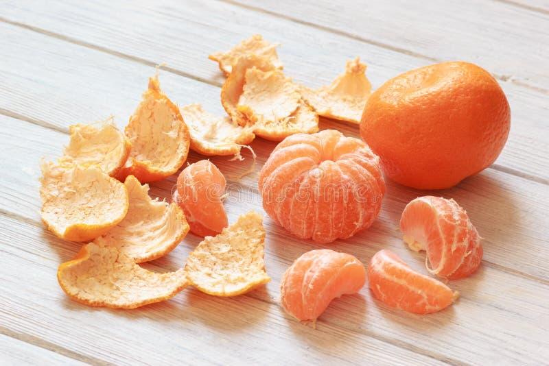 Groupe de mandarines oranges juteuses de mandarine avec la peau épluchée sur la table photos stock