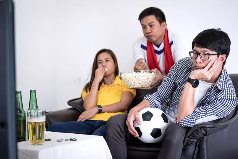 Groupe de match de football de observation de fanclub d'amis sur la TV et le cheerin photographie stock