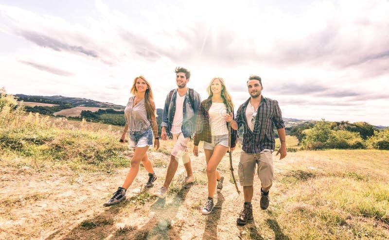 Groupe de meilleurs amis marchant librement sur le pré d'herbe - amitié et concept de liberté avec les jeunes millenial partagean photos libres de droits