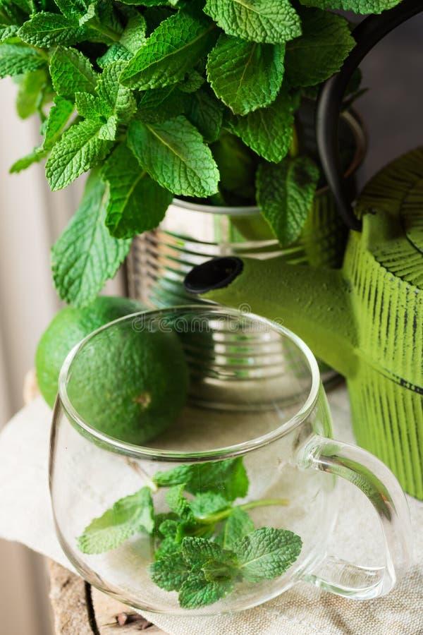 Groupe de menthe fraîche dans la boîte en fer blanc, tasse en verre, pot, chaux sur le tissu de toile, préparant pour brasser la  images stock