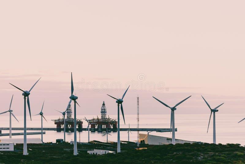 Groupe de moulins à vent et de panneaux solaires pour la production de courant électrique et plates-formes pétrolières sur la côt images stock