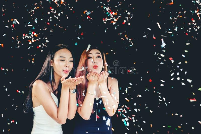 Groupe de partie de célébration de jeune femme asiatique tenant les confettis ha photos stock