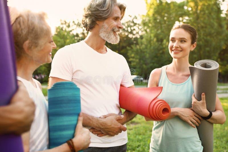 Groupe de personnes avant pratique en matière de yoga de matin image stock