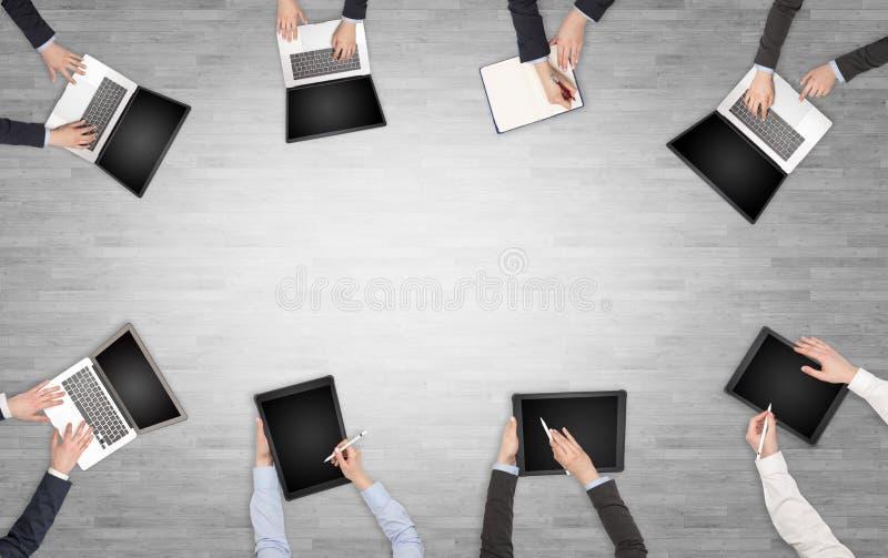 Groupe de personnes avec des dispositifs dans des mains ayant la discussion de bureau et travaillant sur les ordinateurs portable photographie stock