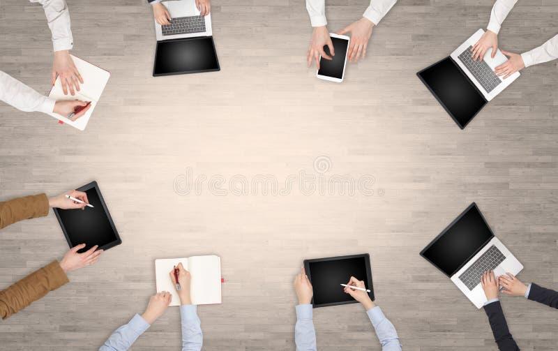 Groupe de personnes avec des dispositifs dans des mains ayant la discussion de bureau et travaillant sur les ordinateurs portable photo stock