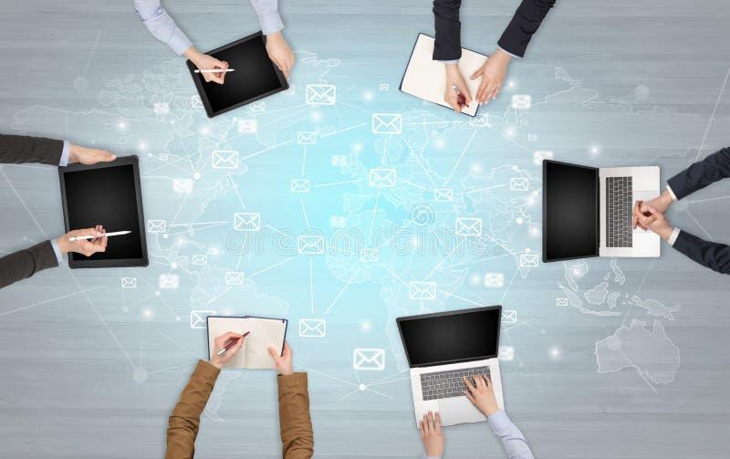 Groupe de personnes avec des dispositifs dans des mains travaillant aux ordinateurs portables et aux comprimés image libre de droits