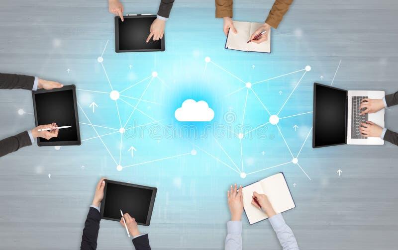 Groupe de personnes avec des dispositifs dans des mains travaillant aux ordinateurs portables et aux comprimés images libres de droits