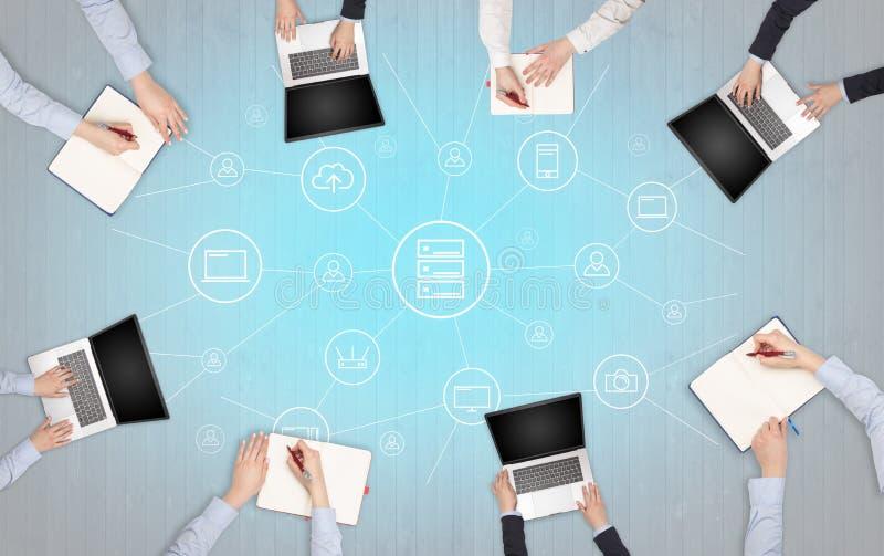 Groupe de personnes avec des dispositifs dans des mains travaillant aux ordinateurs portables et aux comprimés avec le concept de photos libres de droits