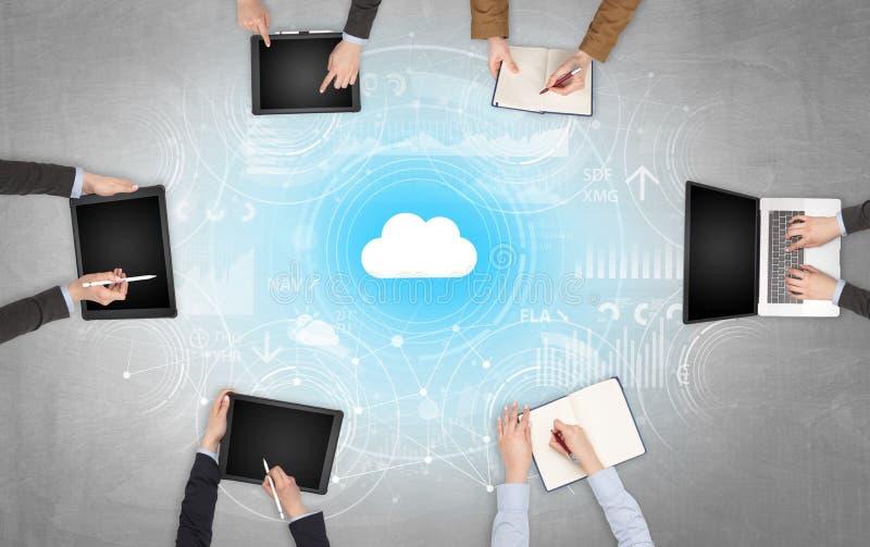 Groupe de personnes avec des dispositifs dans des mains travaillant aux ordinateurs portables et aux comprimés avec le concept en image libre de droits