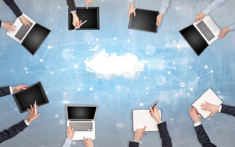 Groupe de personnes avec des dispositifs dans des mains travaillant aux ordinateurs portables et aux comprimés avec le concept en photographie stock