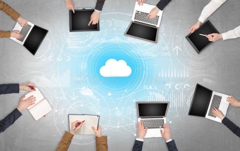 Groupe de personnes avec des dispositifs dans des mains travaillant aux ordinateurs portables et aux comprimés avec le concept en image stock