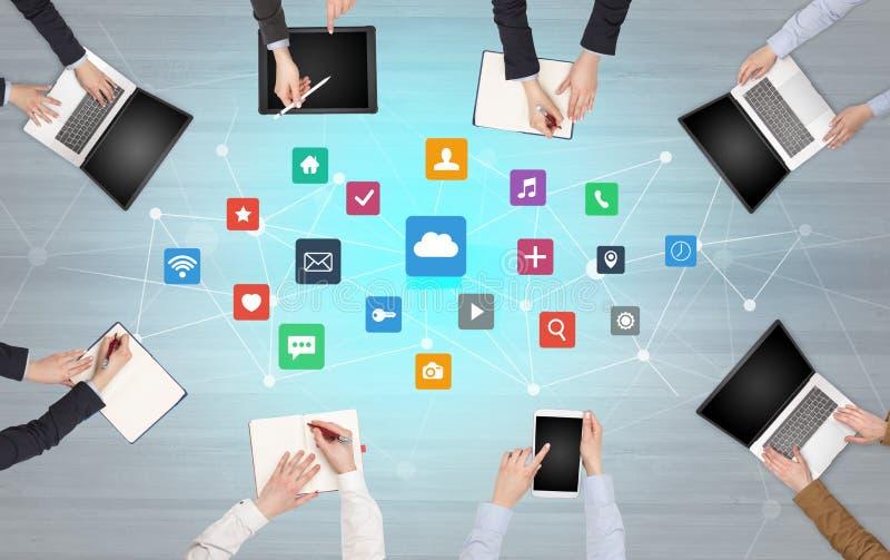 Groupe de personnes avec des dispositifs dans des mains travaillant aux ordinateurs portables et aux comprim?s photo libre de droits