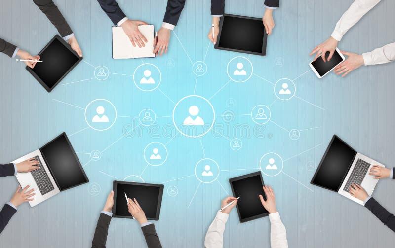 Groupe de personnes avec des dispositifs dans des mains travaillant aux ordinateurs portables et aux comprim?s avec le concept de photo libre de droits