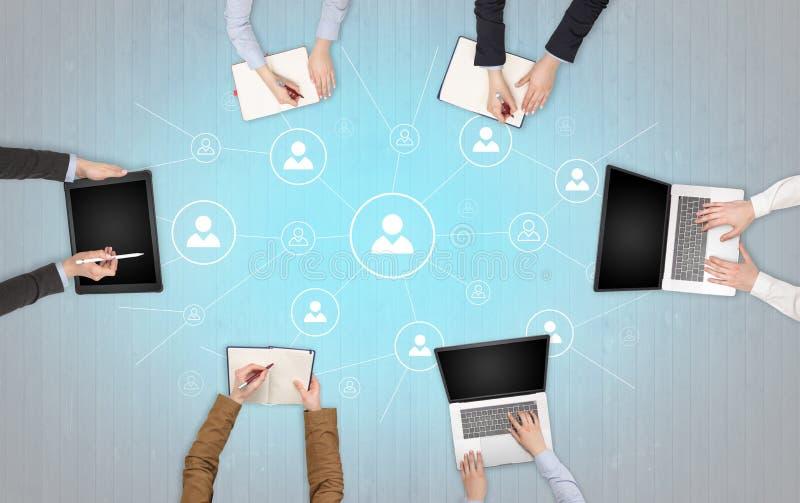 Groupe de personnes avec des dispositifs dans des mains travaillant aux ordinateurs portables et aux comprim?s avec le concept de images libres de droits