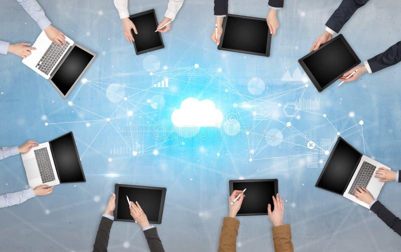 Groupe de personnes avec des dispositifs dans des mains travaillant aux ordinateurs portables et aux comprim?s avec le concept en images stock