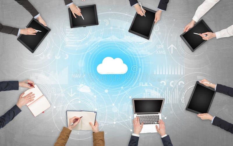 Groupe de personnes avec des dispositifs dans des mains travaillant aux ordinateurs portables et aux comprim?s avec le concept en image stock
