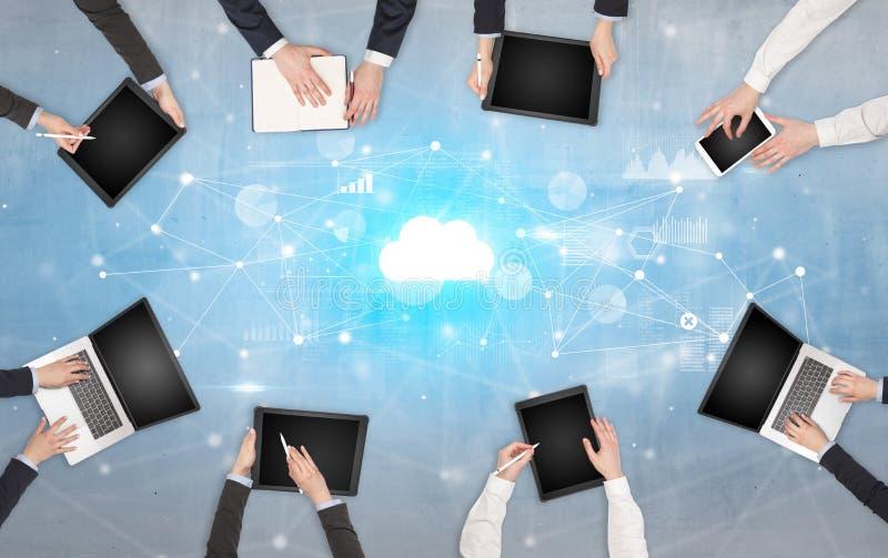 Groupe de personnes avec des dispositifs dans des mains travaillant aux ordinateurs portables et aux comprim?s avec le concept en photos libres de droits