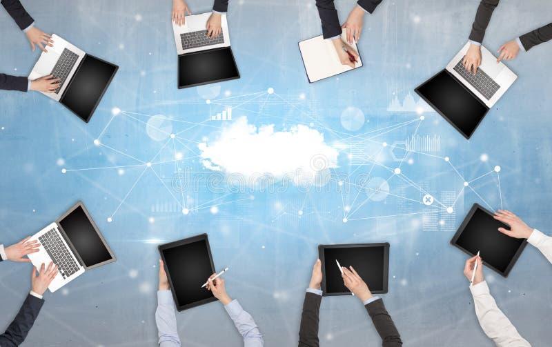 Groupe de personnes avec des dispositifs dans des mains travaillant aux ordinateurs portables et aux comprim?s avec le concept en photo libre de droits