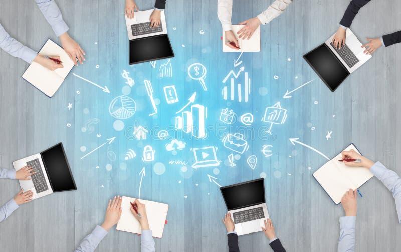 Groupe de personnes avec des dispositifs dans des mains travaillant sur les ordinateurs portables, comprimés dans l'équipe photographie stock