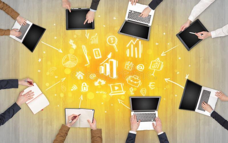 Groupe de personnes avec des dispositifs dans des mains travaillant sur les ordinateurs portables, comprimés dans l'équipe images libres de droits