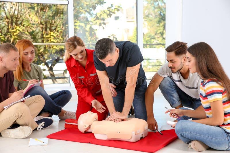 Groupe de personnes avec l'instructeur pratiquant le CPR photo libre de droits