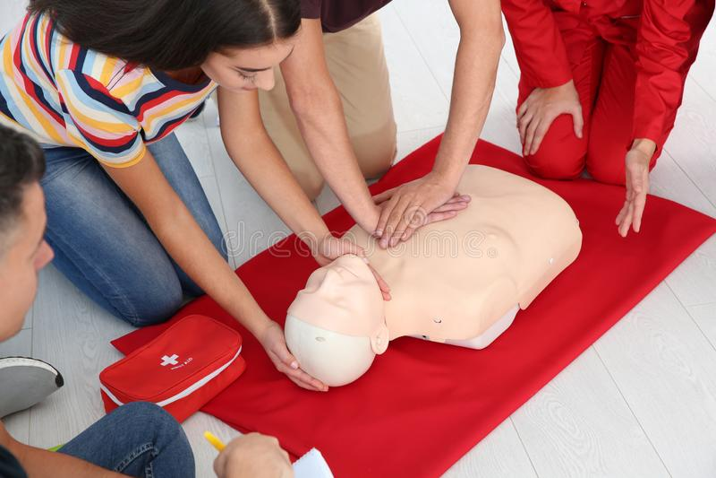 Groupe de personnes avec l'instructeur pratiquant le CPR sur le mannequin à la classe de premiers secours, plan rapproché image stock