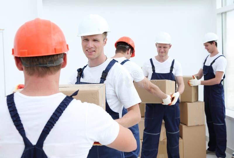 Groupe de personnes constructeurs avec des boîtes images stock