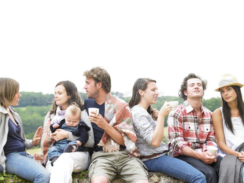 Groupe de personnes détendant à l'extérieur avec du café photographie stock libre de droits