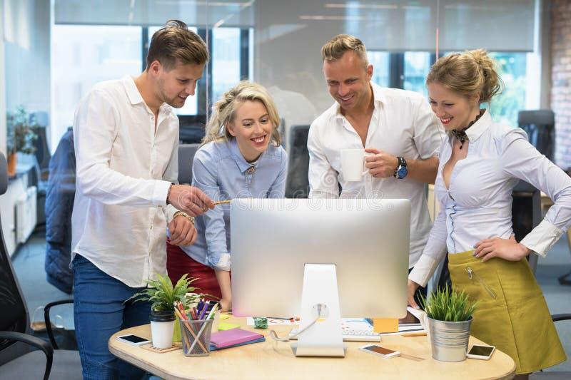 Groupe de personnes dans le bureau regardant l'ordinateur photos libres de droits