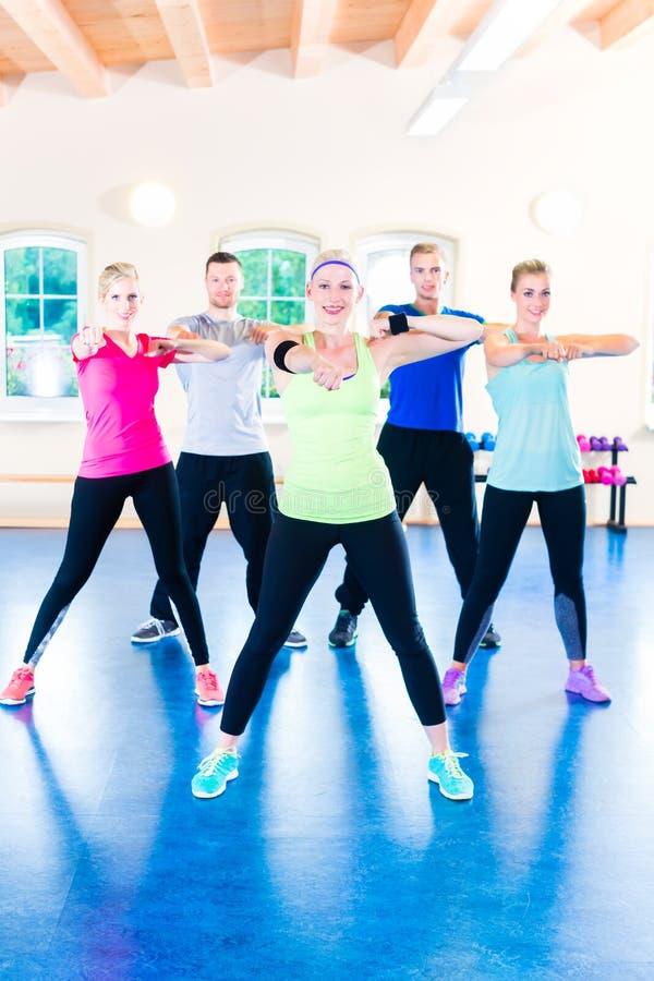 Groupe de personnes de forme physique dans le gymnase à l'aérobic image stock