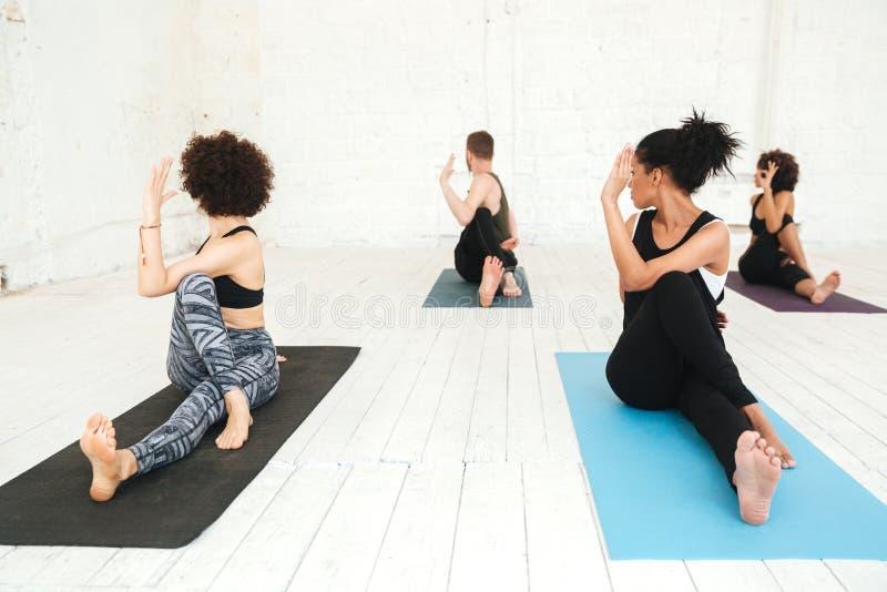 Groupe de personnes faisant le yoga dans le gymnase se reposant sur des tapis de formation images stock