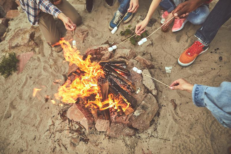 Groupe de personnes faisant les guimauves frites sur le feu photographie stock libre de droits