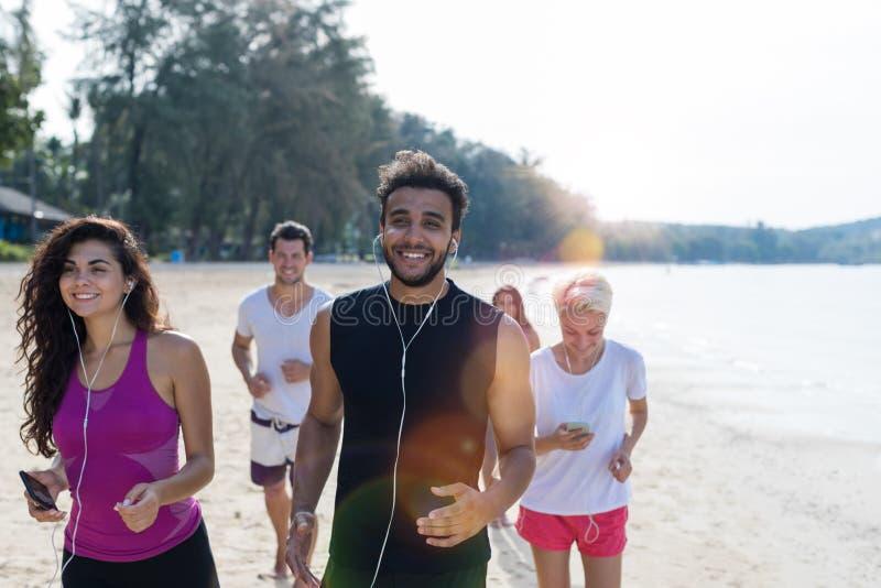 Groupe de personnes fonctionnement, jeunes coureurs de sport pulsant sur la plage établissant le sourire taqueurs masculins et fe images stock