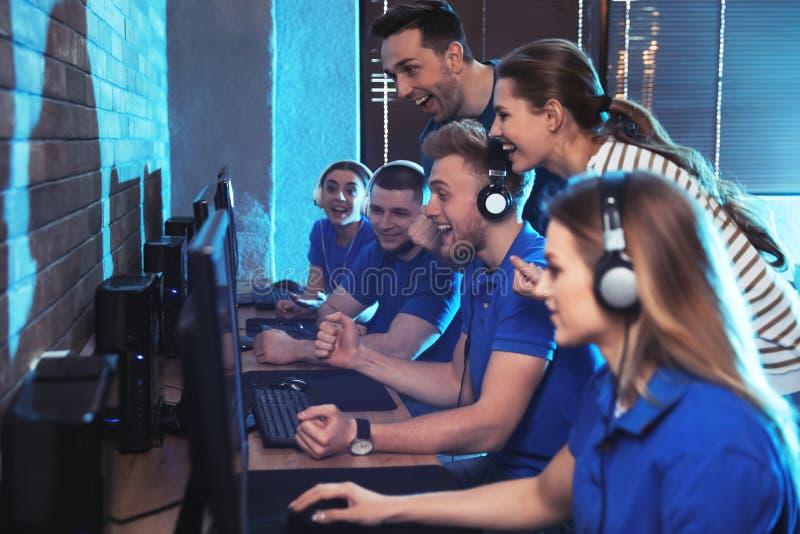 Groupe de personnes jouant des jeux vidéo en café photos stock
