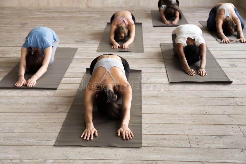Groupe de personnes la leçon de pratique de yoga, faisant l'exercice d'enfant, Ba images stock
