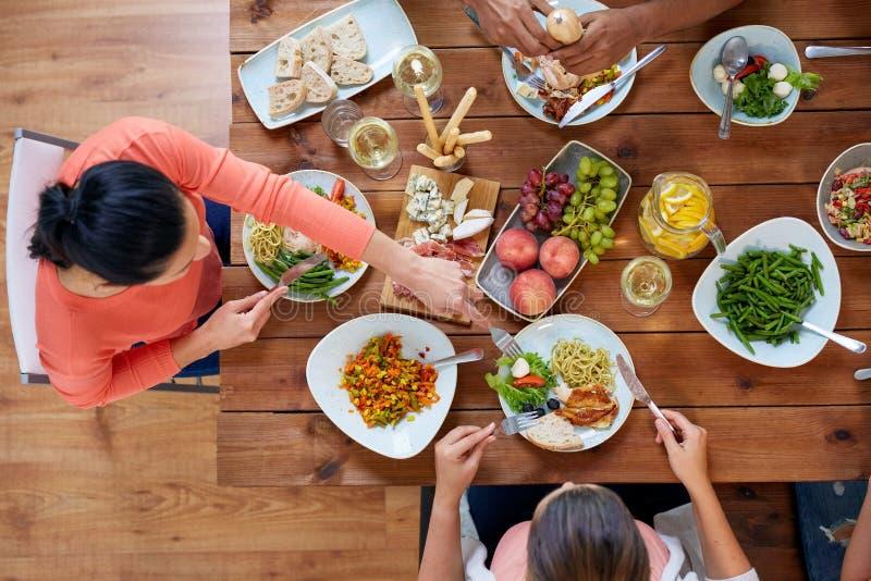 Groupe de personnes mangeant à la table avec la nourriture images libres de droits