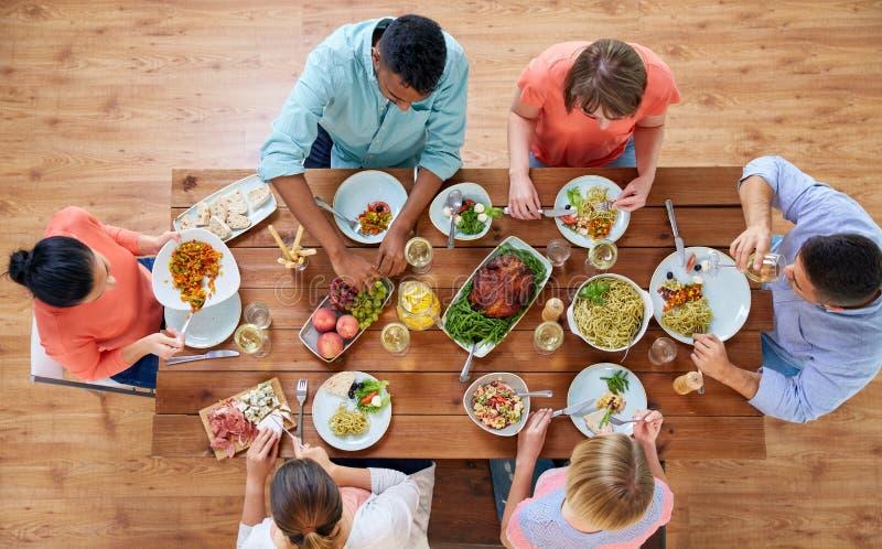 Groupe de personnes mangeant à la table avec la nourriture photographie stock libre de droits