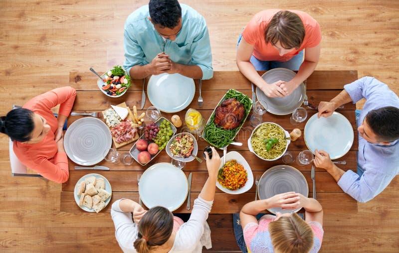 Groupe de personnes mangeant à la table avec la nourriture image stock