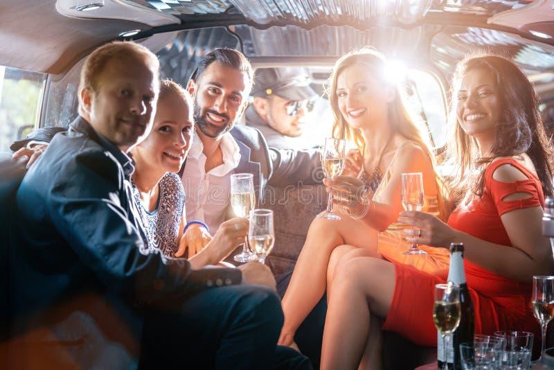 Groupe de personnes de partie dans un boire de limousine photo stock
