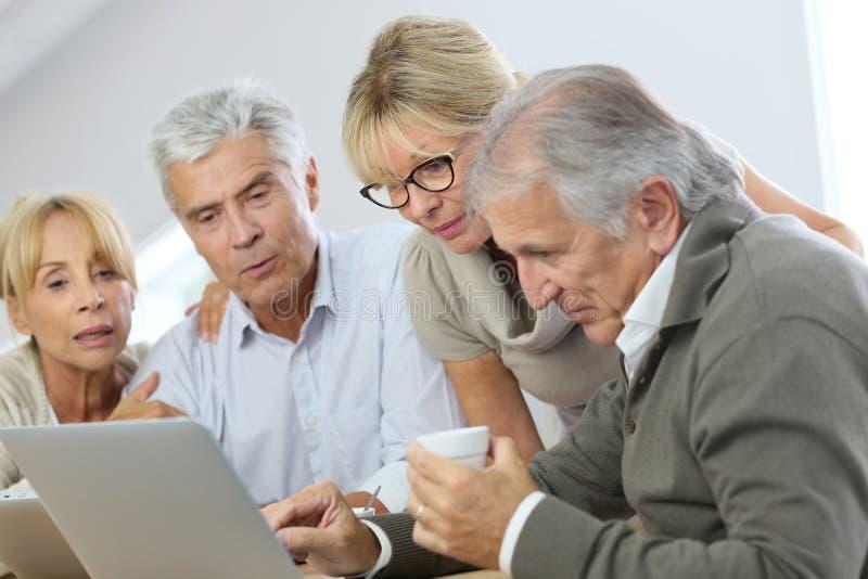 Groupe de personnes retraitées à la maison utilisant l'ordinateur portable photos stock